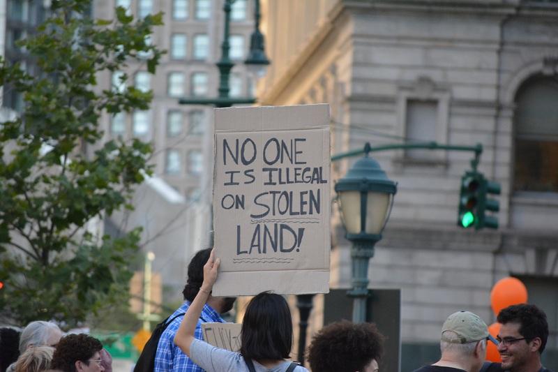 """Lights4Liberty, manifestação em Nova York do dia 12 de julho. Cartaz diz: """"Ninguém é ilegal em uma terra roubada!"""". Foto: Christopher Penler / Shutterstock.com"""